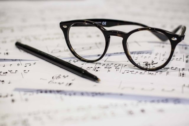 Glasses, pen resting on sheet music.