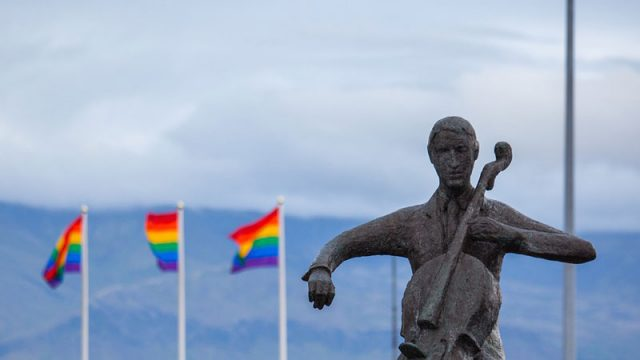 Pictured: Statue of man playing cello with rainbow flags in background.
