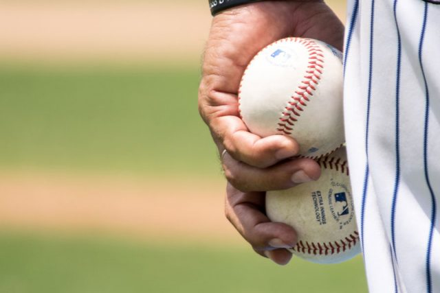 Baseball player holding two baseballs in left hand. Photo by Jose Morales.