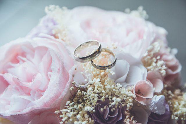 Gold-colored bridal ring set on pink rose flower bouquet. Photo by Beatriz Pérez Moya.