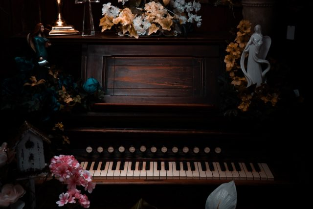 Piano in home surrounded by flowers and small statues. Photo by Miguel Dominguez.