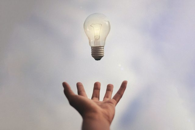 Lightbulb floating over a hand Photo by Júnior Ferreira.