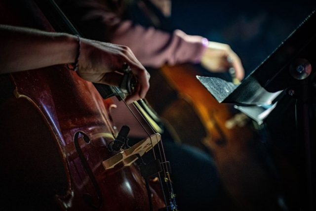 Close up of cellist playing on stage by Rob Simmons.