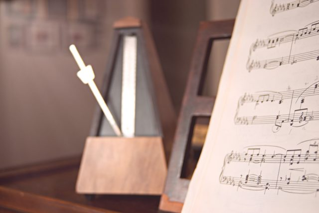 Metronome with sheet music on music stand. Photo by Rachel Loughman/Unsplash.