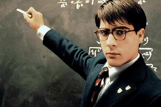 Still from movie Rushmore with Jason Schwartzman standing at chalkboard with arm extended holding chalk in his right hand, staring menacingly into camera.