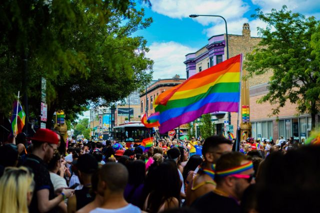Photo of people on the street carrying rainbow flag.